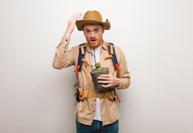 Homem novo do explorador do ruivo preocupado e oprimido. ele está segurando uma cantina.