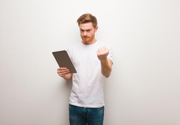 Homem novo do ruivo que mostra o punho para frontear, expressão irritada. segurando um tablet.
