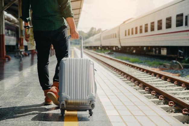 Homem novo do turista que anda bagagem do arrasto. outra mão segurando o mapa e caminhando para o trem