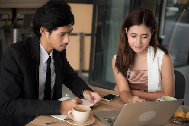 Homem novo e mulher asiáticos que procuraram dados no internet com o laptop no café.
