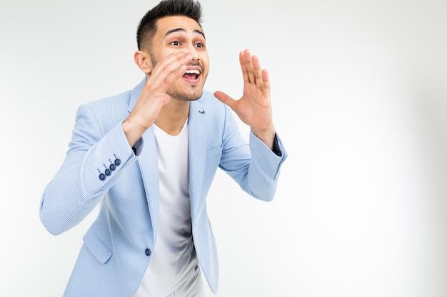 Homem novo em um casaco azul que grita a notícia em um fundo branco com espaço da cópia