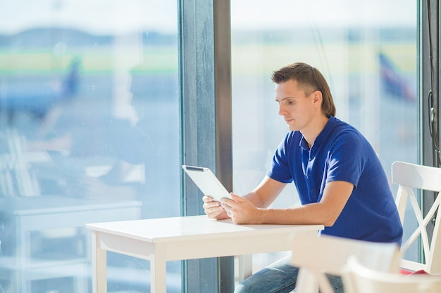 Homem novo em uma sala de estar do aeroporto que espera o avião do voo.