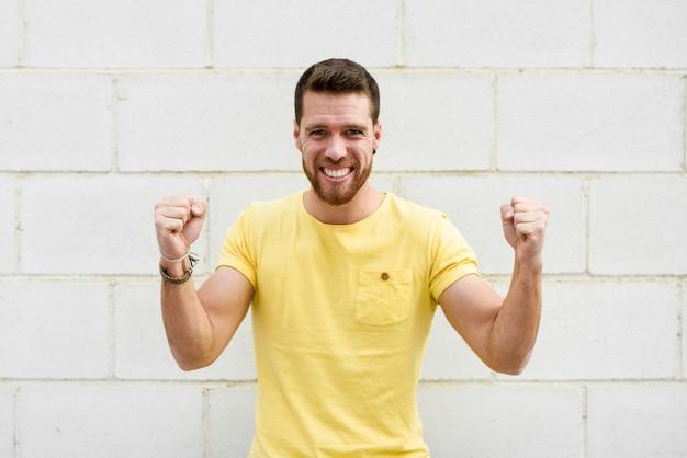 Homem novo engraçado na parede de tijolo com expressão engraçada.