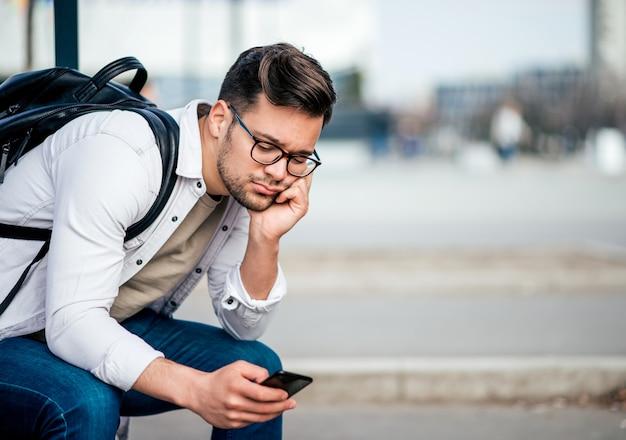 Homem novo entediado ocasional com o backcpack que senta-se no banco e que espera o ônibus, usando o smartphone.