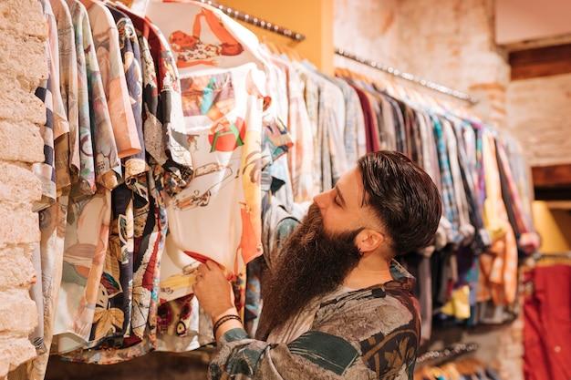 Homem novo farpado que escolhe a camisa que pendura no trilho na loja