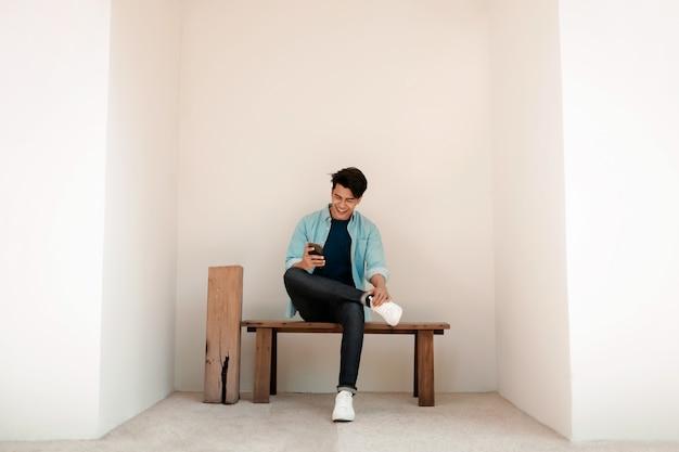 Homem novo feliz no desgaste ocasional usando o telefone celular ao sentar-se no banco pela parede. estilo de vida das pessoas modernas.