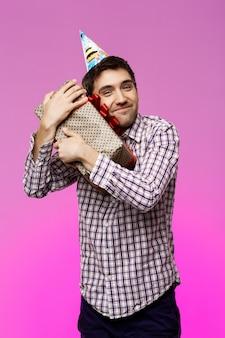 Homem novo feliz que abraça o presente de aniversário na caixa sobre a parede roxa.