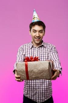 Homem novo feliz que guarda o presente de aniversário na caixa sobre a parede roxa.