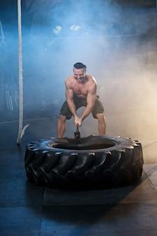 Homem novo forte que bate o pneu da roda usando o martelo no gym.