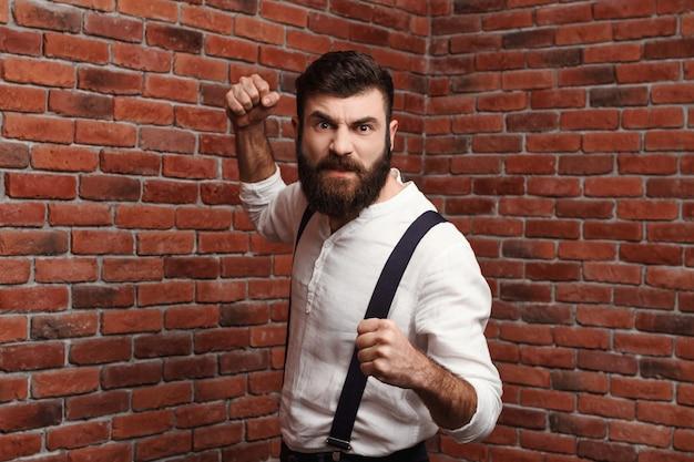 Homem novo furioso da raiva que mostra os punhos que levantam na parede de tijolo.