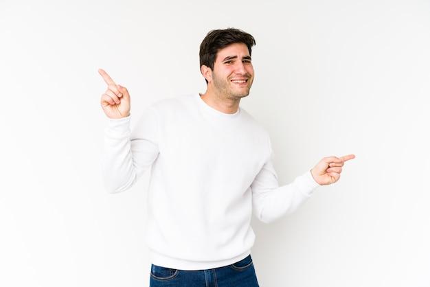 Homem novo isolado no branco que aponta aos espaços diferentes da cópia, escolhendo um deles, mostrando com o dedo.