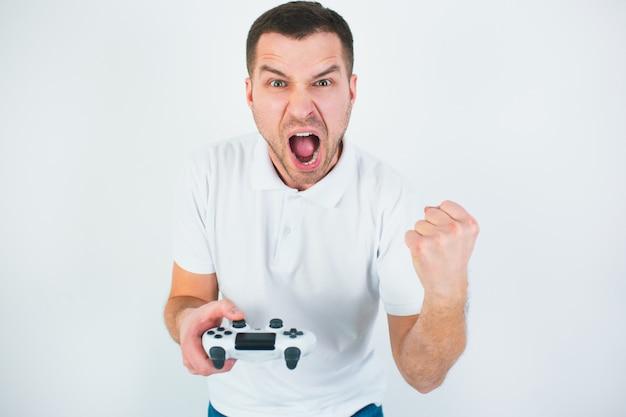 Homem novo isolado sobre a parede branca. cara gritando e gritando. vencendo em jogo de computador. gritando em voz alta e olhando para a câmera. jogando jogos durante a quarentena.