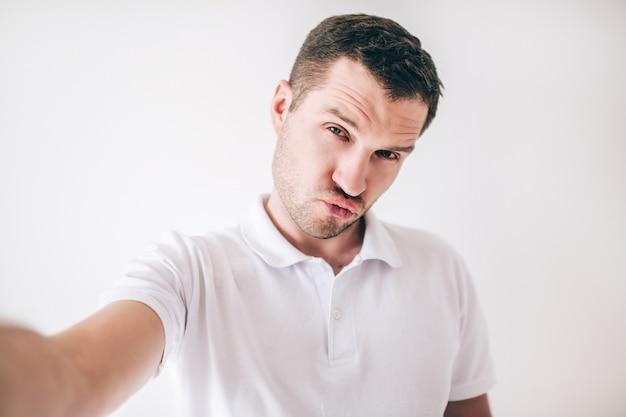 Homem novo isolado sobre a parede branca. cara segura a câmera com a mão e tira uma selfie ridícula. homem posando com os lábios segurando juntos. expressão facial engraçada.