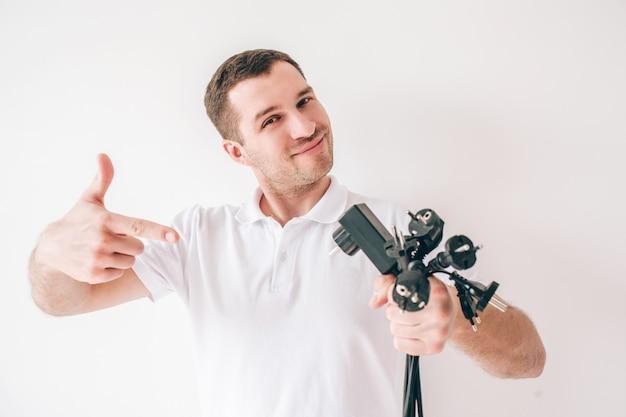 Homem novo isolado sobre a parede branca. cara segura cabos de entrada pretos e cabos elétricos em hans e aponta para eles. posando na câmera.