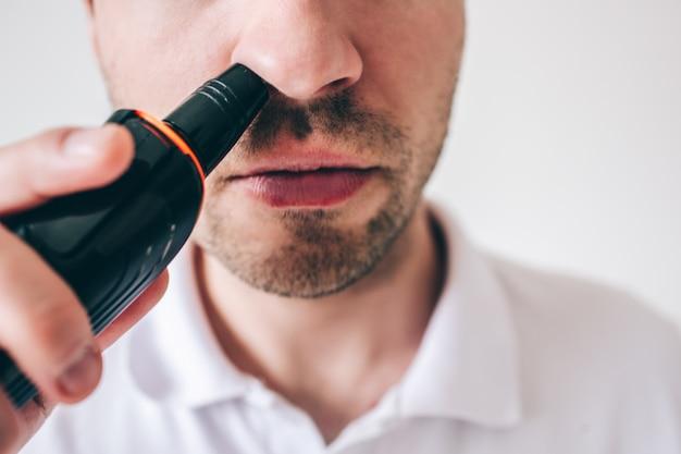 Homem novo isolado sobre a parede branca. close-up e corte a vista do cara remover o cabelo do nariz com o aparador. trabalho cuidadoso e preciso.