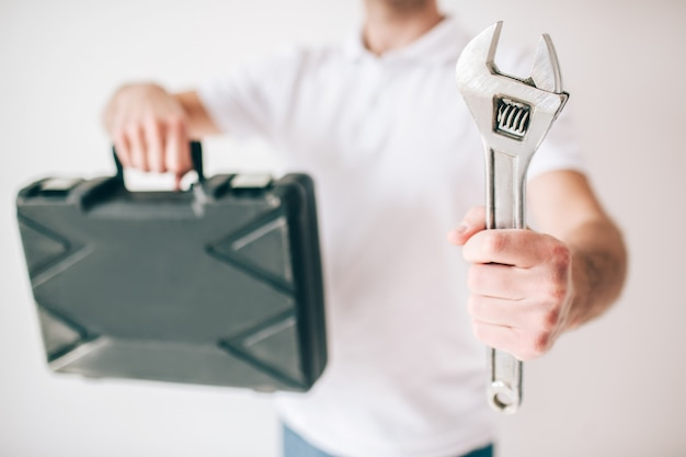 Homem novo isolado sobre a parede branca. corte a vista do cara segurando a caixa e a chave nas mãos. reter o homem de encanador de fixação.
