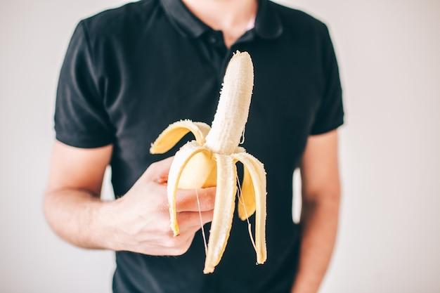 Homem novo isolado sobre a parede branca. corte a vista e feche a banana madura amarela descascada nas mãos do cara. deliciosa fruta deliciosa.