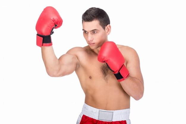 Homem novo muscular com luvas de boxe em roupa de esportes.