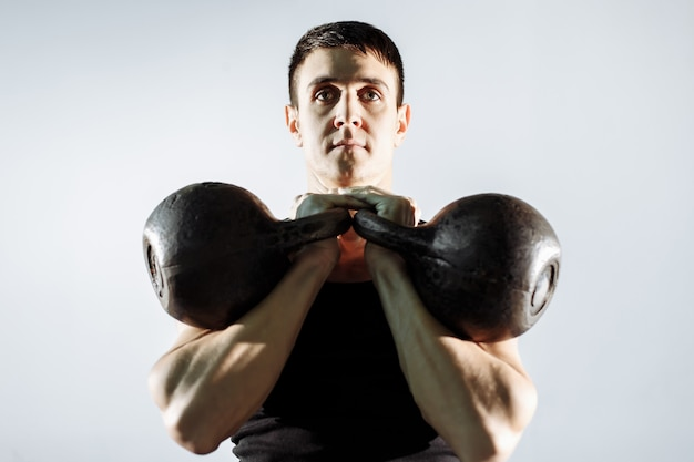 Homem novo muscular que faz o exercício pesado para o bíceps.