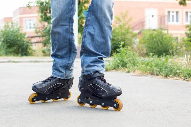 Homem novo na calças de ganga que monta patins de rolo na cidade. fechar as pernas