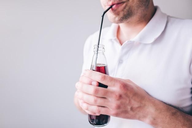 Homem novo na camisa branca isolada. corte a vista do cara bebendo coca-cola com canudo de plástico. segurando a garrafa nas mãos.