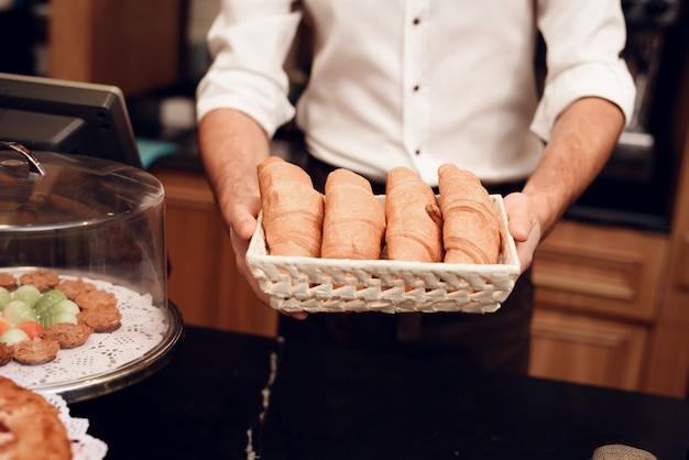 Homem novo no avental que está com pão na padaria.