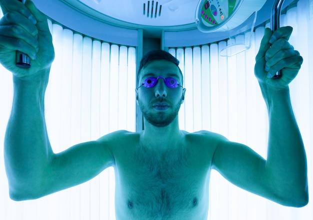 Homem novo no solário no salão de beleza.