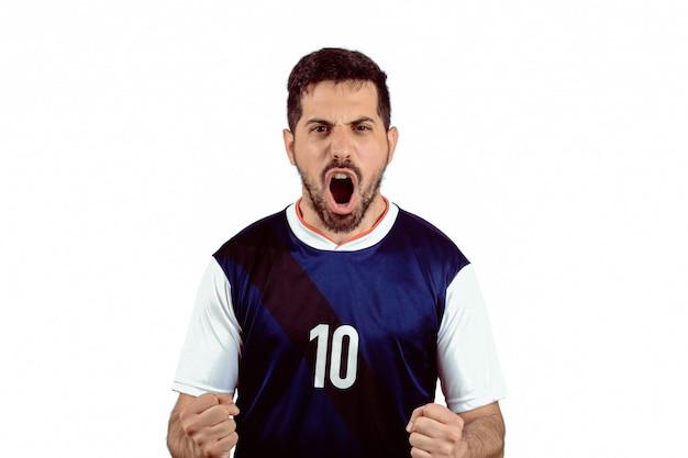 Homem novo no uniforme do futebol do futebol que grita quando sua vitória da equipe.