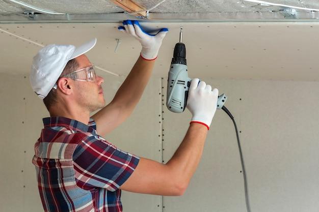 Homem novo nos óculos de proteção que fixa drywall suspendeu o teto à armação de metal usando a chave de fenda elétrica no teto isolado com folha de alumínio brilhante. renovação, construção, faça você mesmo conceito.