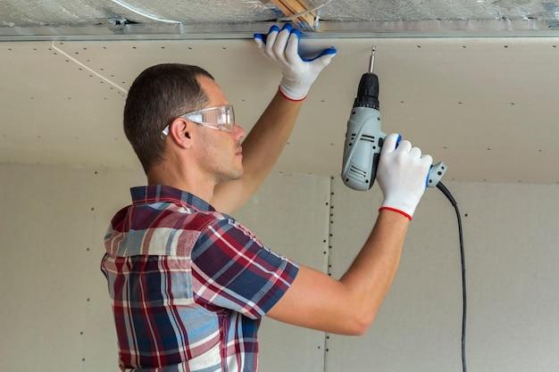 Homem novo nos óculos de proteção que fixa o drywall suspendeu o teto à armação de metal usando a chave de fenda elétrica no teto isolado com folha de alumínio brilhante. renovação, construção, faça você mesmo conceito.