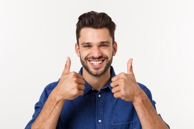 Homem novo ocasional feliz que mostra o polegar acima e o sorriso isolado.