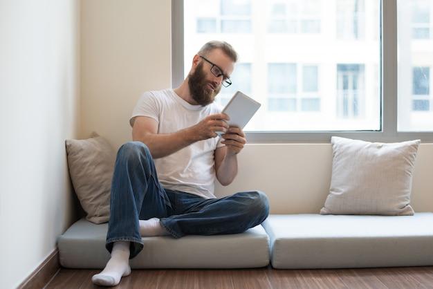 Homem novo pensativo sério nos vidros que lê o artigo em linha