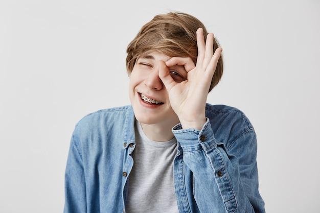 Homem novo positivo com o cabelo louro que fecha os olhos e que sorri com a alegria que mostra o sinal aprovado que está contente após ter encontrado sua namorada isolada contra o fundo cinzento. expressões e emoções do rosto humano