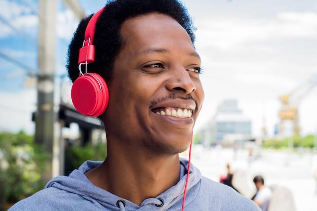 Homem novo que aprecia a música ao ar livre.