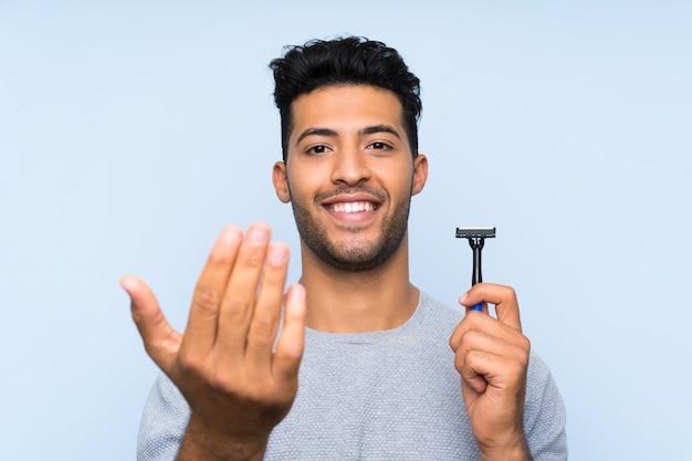 Homem novo que barbeia sua barba sobre a parede azul isolada que convida a vir com a mão. feliz que você veio