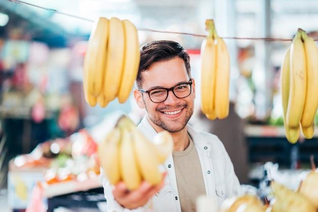 Homem novo que compra ou que vende bananas no mercado do fazendeiro.