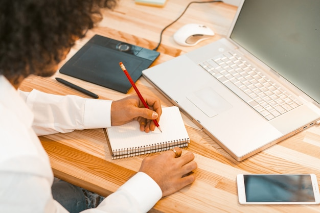 Homem novo que escreve no local de trabalho do bloco de notas em casa. cara árabe trabalha na mesa de madeira com laptop, tablet digital e smartphone nele.