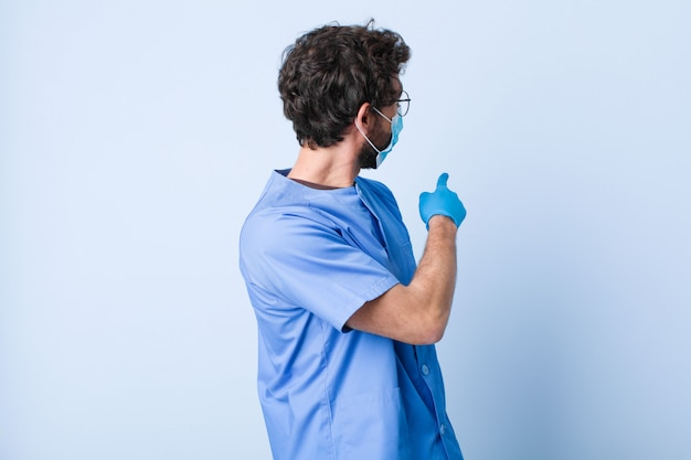 Homem novo que está e que aponta ao objeto no espaço da cópia, vista traseira. conceito de coronavírus