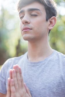 Homem novo que está no pose da ioga ao ar livre