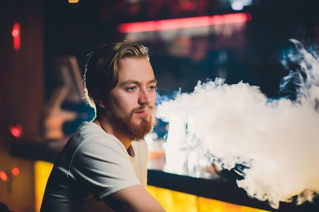 Homem novo que fuma shisha no restaurante árabe - homem que exala a fumaça que inala de um cachimbo de água.