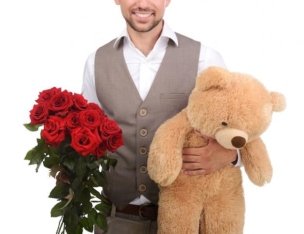 Homem novo que guarda um brinquedo e rosas enchidos.
