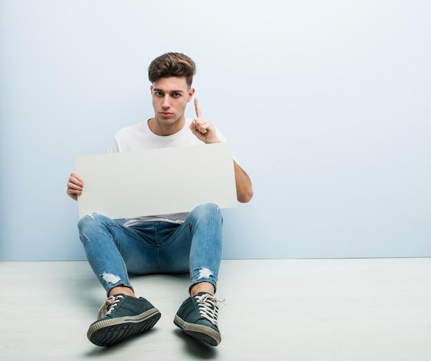 Homem novo que guarda um cartaz que senta-se em seu assoalho home que mostra o número um com dedo.