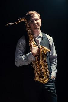 Homem novo que joga o saxofone