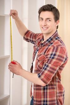 Homem novo que mede a mobília home com medida da fita.