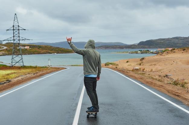 Homem novo que monta um longboard na estrada vazia no verão, vista traseira da montanha.