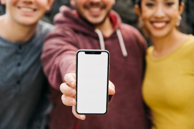 Homem novo que mostra o espaço vazio do smartphone ao estar perto dos amigos multirraciais