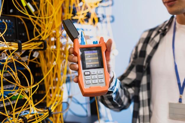 Homem novo que mostra o verificador da fibra óptica