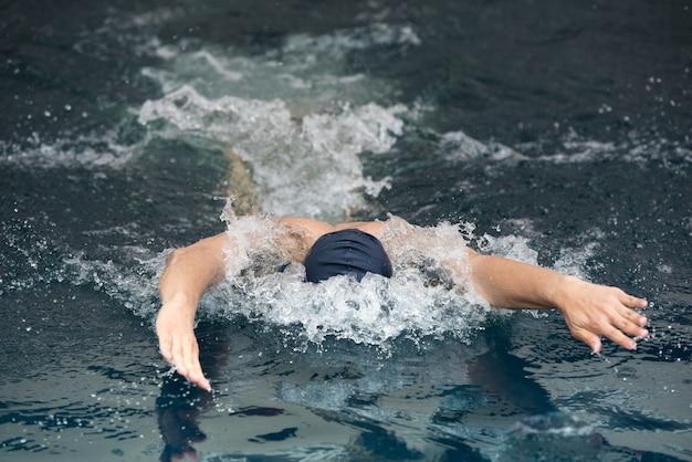 Homem novo que nada o curso de borboleta em uma piscina.