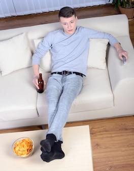 Homem novo que olha a tevê e que bebe a cerveja em casa.
