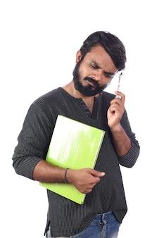 Homem novo que pensa sobre algo para escrever no diário isolado na superfície branca.